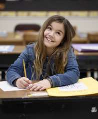 back-to-school-girl-sitting-at-desk-smiling-in-classroom_t20_gRkjXk