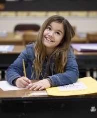 back-to-school-girl-sitting-at-desk-smiling-in-classroom_t20_gRkjXk